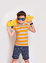 Cute little guy in big trendy sunglasses and yellow longboard. Kid boy posing with his skateboard against white wall with copyspace.