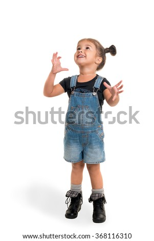 Cute little happy girl standing and looking up on  white background