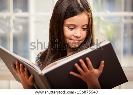 Cute little Hispanic girl reading a story from a big book in the living room
