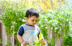 Cute little Indian asian boy playing in garden with flowers in hand. curious expression.