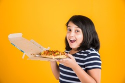 Cute little Indian/Asian girl child eating tasty Burger, Sandwich or Pizza in a plate or box. Standing isolated over blue or yellow background.