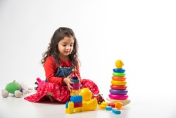Cute Little Indian / Asian girl playing with colourful block toys over white background