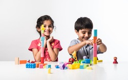 Cute little Indian asian kids playing with colourful plastic toys or blocks while sitting at table or isolated over white background