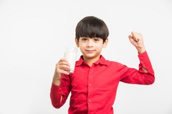 Cute little Indian/Asian playful boy holding or drinking a glass full of Milk, isolated over  white background