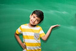 cute little indian/asian school boy presenting something over green chalkboard background with copy space