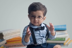 Cute little Indian genius. Baby boy wearing smart outfit and eye glasses working front of many books. He is very happy and smiling. Child concept, closeup