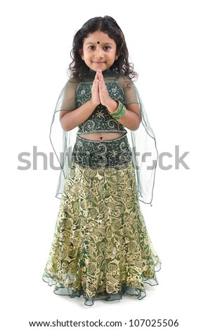 Cute little Indian girl in a greeting pose, isolated white background ...