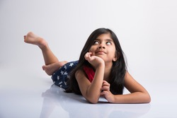 Cute little Indian girl lying on the floor resting her head in her hands, isolated over white background