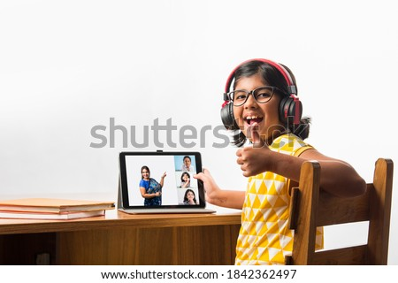 Cute Little Indian girl studying online using her laptop or Tablet computer at home or attending school during corona pandemic or lockdown