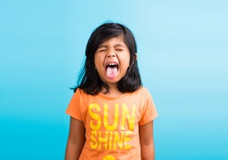 Cute little Indian girl with funny expressions posing for photoshoot, against sky blue background
