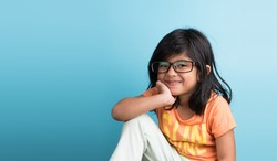 Cute little Indian girl with spectacles smiling and posing for photoshoot, against sky blue background