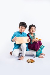 Cute little Indian Sister tying Rakhi to Her little brother's wrist and exchanging gifts and sweets on Raksha Bandhan or Bhai Dooj festival, Sitting isolated over white background