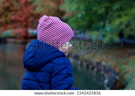 Cute little kid boy in warm autumn clothes having fun outdoor. Active leisure with kids. Active leisure with kids at parck.