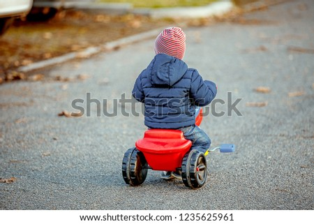 Cute little kid boy in warm autumnal clothes turned from behind having fun with tricycle. Active leisure with kids. Active leisure with kids outdoor.