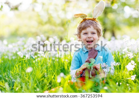 Cute little kid boy with Easter bunny ears celebrating traditional feast. Happy child  eating chocolate figure on sunny day. Family, holiday, spring , carefree childhood concept.