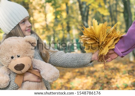 Cute little kid daughter congratulating mum with mothers day, smiling girl with Teddy bear presents autumn yellow leaves, handing them to mother. Bouquet present for birthday, Mother's Day concept #1548786176