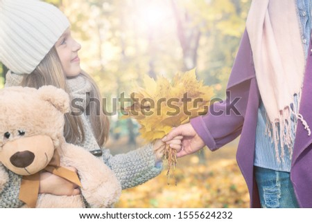 Cute little kid daughter congratulating mum with mothers day, smiling girl with Teddy bear presents autumn yellow leaves, handing them to mother. Bouquet present for birthday, Mother's Day concept #1555624232