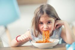 Cute little kid girl eating spaghetti bolognese at home.