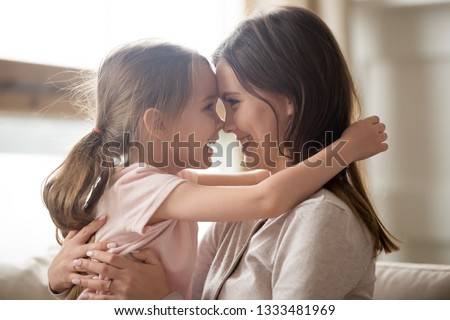 Cute little kid girl embracing smiling mom touching noses having fun cuddling, happy affectionate family mother and funny little child daughter laughing bonding playing feel joy connection at home
