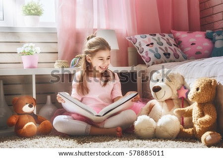 Cute little kid girl is reading a book at home. Funny lovely child having fun in kids room.  #578885011