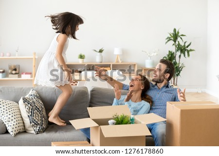 Cute little kid girl jumping on sofa excited on moving day, family mom dad child laughing having fun in new home unpacking boxes, happy daughter playing helping parents to pack enjoying relocation