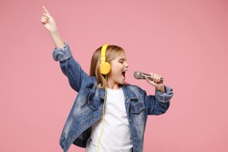 Cute little kid girl 12-13 years old isolated on pastel pink background. Childhood lifestyle concept. Mock up copy space. Listen music with headphones sing song in microphone pointing index finger up