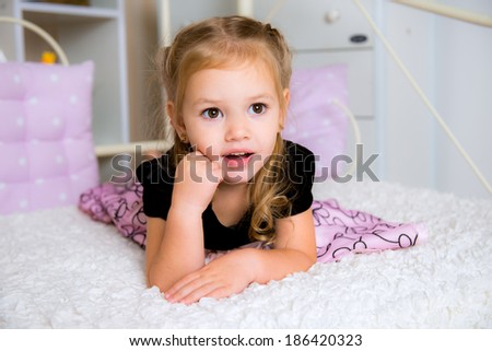 Cute little kid in dress on the bed