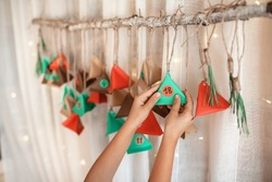 Cute little kid opening handmade advent calendar with color paper triangles. Sweets hidden in colorful triangles hanging on branch. Seasonal activity for kids, family winter holidays, focus on hand