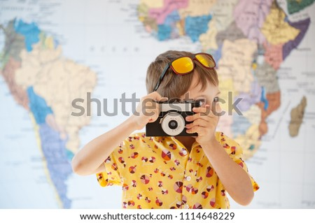 cute little kid photographer taking picture with vintage film camera on world map backdrop