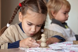 Cute little kid playing with modeling clay in pottery workshop, craft and clay art, child creative activities, education in Arts