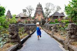 Cute little kid running and having fun in Pura Taman Saraswati temple, also known as the Lotus temple, Ubud, Bali, Indonesia.