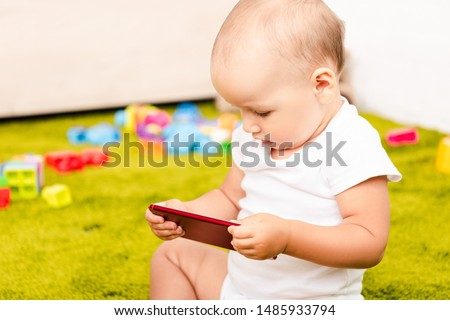 Cute little kid sitting on green floor with toys and holding digital device #1485933794