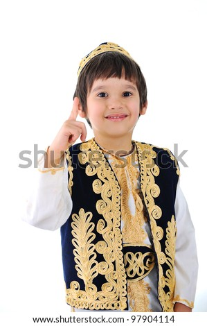 Cute little kid wearing traditional middle-east clothes finger pointing - stock photo