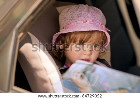 cute little kid with serious expression sitting on safety car seat