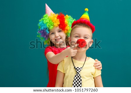 Cute little kids in funny disguise on color background. April fool's day celebration