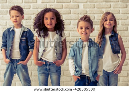 Cute little kids in stylish jeans clothes are looking at camera and smiling, standing with hands in pockets against white brick wall #428585380