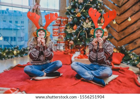 Cute little kids looking through reindeer antlers headgear, making fun on new year evening.