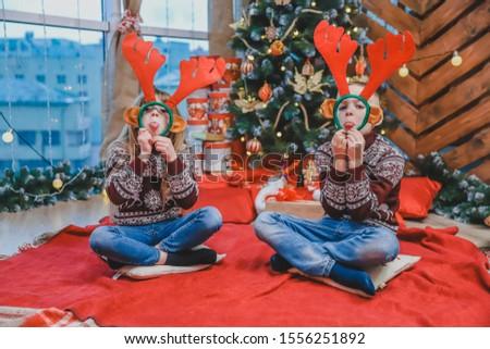Cute little kids looking through reindeer antlers headgear, making grimaces on new year evening.