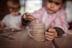 Cute little kids playing together with modeling clay in pottery workshop, craft and clay art, child creative activities, education in Arts