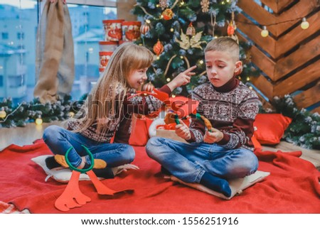 Cute little kids playing with reindeer antlers headgear, making fun on new year evening.