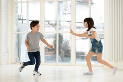 Cute little kids siblings playing tag and touch game at home, two excited happy small children boy and girl running laughing catching each other in funny activity inside modern living room indoor