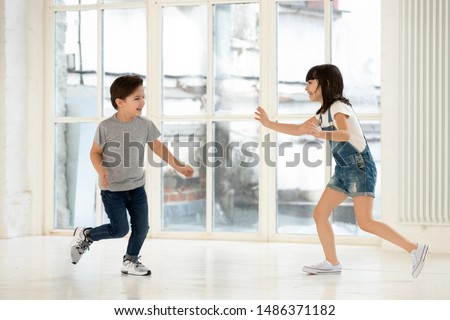 Photo of Cute little kids siblings playing tag and touch game at home, two excited happy small children boy and girl running laughing catching each other in funny activity inside modern living room indoor