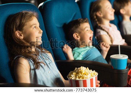 Cute little kids smiling joyfully watching a movie at the cinema entertainment childhood kids comedy cartoons family recreation leisure activity holidays positivity emotions concept  #773743075