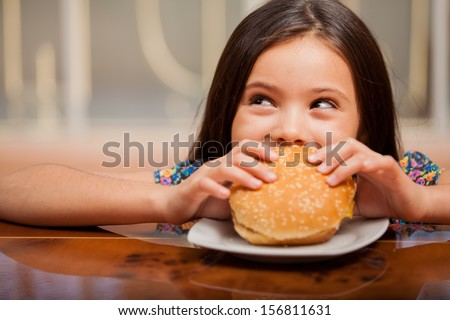 Cute little Latin girl eating a hamburger and looking up towards copy space