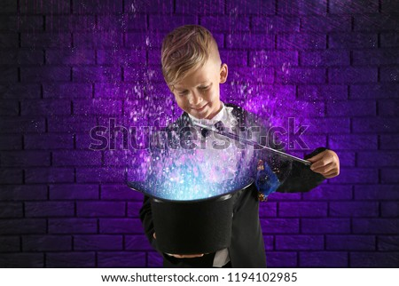 Cute little magician showing trick with hat against dark brick wall