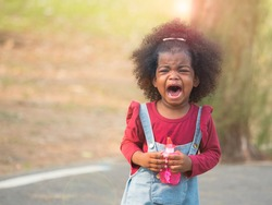 Cute little mix race African girl crying alone in the park, loosing from parents or throwing tantrum.