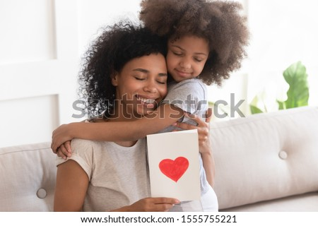 Cute little mixed race ethnicity girl hug young african American mom present handmade postcard with heart, loving small biracial daughter congratulate mother give greeting card, hug cuddle at home