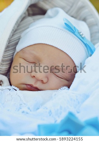 Cute little newborn baby boy wearing white hat with a blue ribbon sleeping wrapped in blue-white wrap. Baby boy, newborn, infant, neonatal, pediatric, innocence and new life concept. Stock photo ©