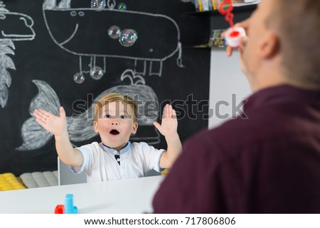 Cute little playfull toddler boy amazed by milky bubbles at child therapy session. Private one on one homeschooling with didactic aids. #717806806