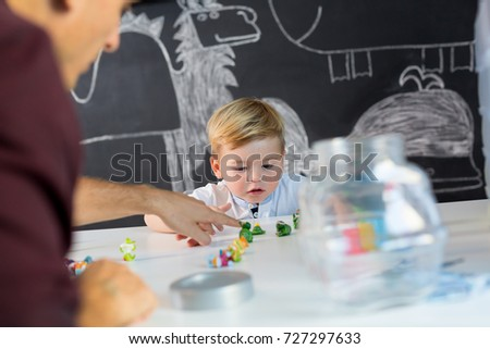 Cute little playfull toddler boy at child therapy session. Private one on one homeschooling with didactic aids. #727297633
